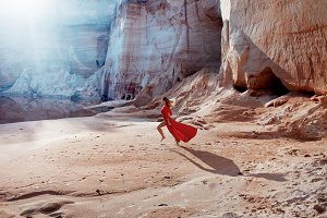 Woman in red waving dress with flying fabric runs on the background of sands career