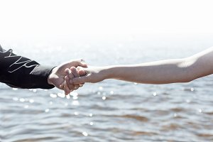 boy and girl are holding hands on the sea background