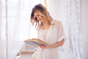 Woman reads a book sitting on bed. Young beautiful girl in her bedroom