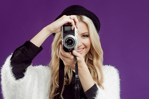 Happy young girl makes the photo. Purple background. Photographer