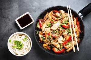 Chicken Stir fry and udon noodles on black.