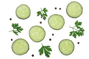 slices of cucumber with leaf parsley and peppercorn isolated on white background