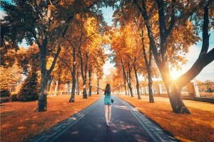 Beautiful view on the autumn trees alley and happy young girl