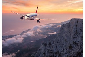 Airplane is flying over rocks and clouds at sunset
