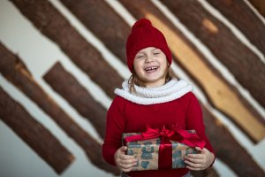 child  in red hat with present