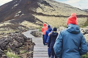 tourists walk along the trail among the lava field in Iceland