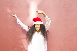 afro girl with santa hat dancing on the street