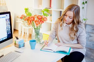 Young businesswoman sitting at desk and working. Beautiful woman fills planner