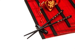 Black chopsticks on red bamboo mat