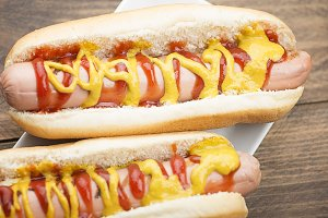 Close-up of two hotdogs on wooden table. Fastfood.