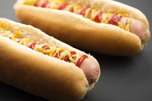 Close-up of two hotdogs with ketchup and mustard on black background. Fastfood.