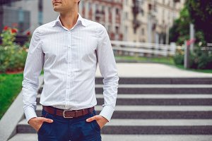 Young male businessman in shirt and blue pants.