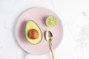 Avocado & Lime Halves On Pink Plate
