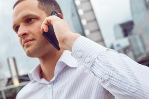 Close up portrait of serious businessman talking on mobile phone.