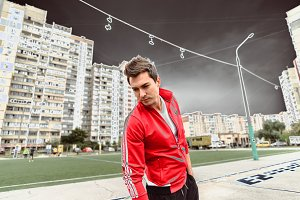 Young man in a red sports suit against the backdrop of a city