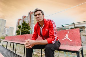 Young man in a red sports suit is sitting on a sports