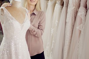 Beautiful young woman in a Bridal salon, choose dress on the mannequin