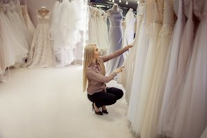 Beautiful girl chooses her wedding dress. Young woman entrepreneur. Portrait in Bridal salon
