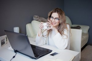 Student or freelancer, working at home with laptop. Charming young woman sits in front of monitor with Cup of coffee.