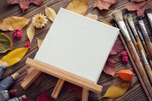 Canvas, paints, brushes and leaves.