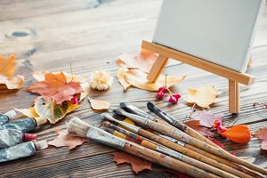 Canvas, brushes and yellow leaves.