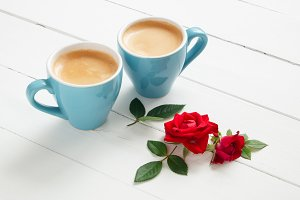 Two espresso coffee cups and roses