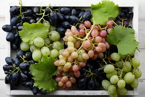 Fresh grapes in white wooden tray