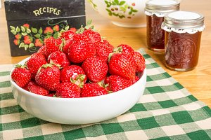 Strawberries with jars of jelly