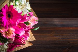 A bouquet of flowers from lily, gerbera, white roses and alstroemeria on a brown wooden table. A holiday, a gift.
