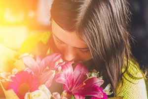Beautiful girl with dark hair with a bouquet of flowers from a lily, gerbera, white roses and alstroemeria on a dark background. A holiday, a gift.