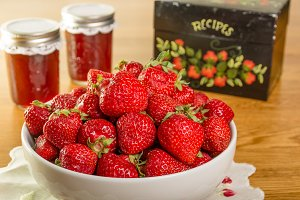 Strawberries with jars of jam
