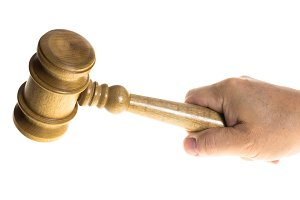 Wooden gavel and hand