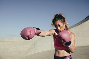 Sportswoman training boxing outdoors