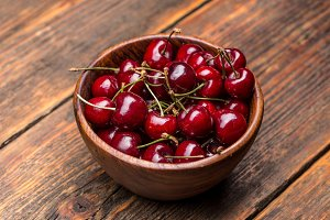 Wooden bowl full of cherries