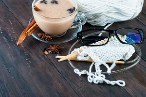 Cup of tea with milk and knitting
