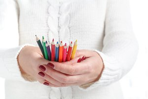 Colored pencils in hand woman