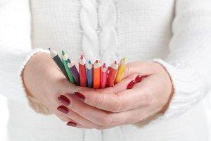 Hand holding colour pencils