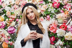 Young beautiful blonde woman in fashionable hat on floral background with coffee to go