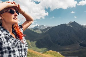 A young woman with glasses raised her hands to her head, stands on the top of the mountain and enjoys the view of the mountains in summer