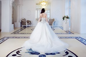 Beautiful bride. Wedding dress with open back. Luxurious light interior