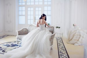 Beautiful girl bride in a magnificent dress sitting on the sofa. Luxurious light interior
