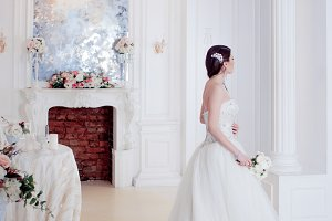 Portrait of beautiful bride. Wedding dress with open back. Luxurious light interior