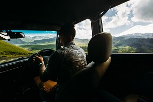 A young man autotravel manages a car against a backdrop of a picturesque mountain landscape in summer, a rear view from a car
