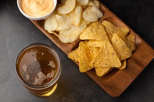 Beer in glasses closeup on the concrete table. Beer and snacks are chips and nachos with cheese souce top view. Drink and snack for the football match or party