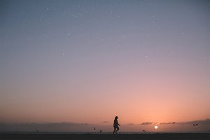 Girl walking on beach with stars