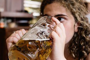Young adult woman is drinking a big beer jar in resturant with b