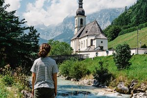 Beautiful girl looking at alpine landscape with church
