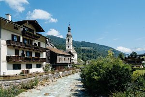 Scenic view of small village and white church in the Alps
