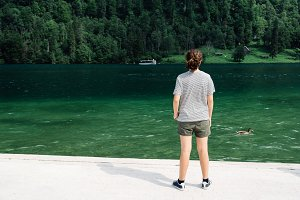 Young woman standing by beautiful lake