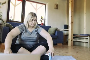 Unhappy overweight woman at home wanting to work out with barbells.